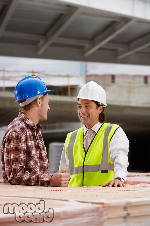 Construction workers talking at building site