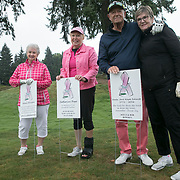 Joyce Bowden stands by a memorial sign for Nanci Ericson, Julie Beaton for her mother, Catherine Pope, and Craig and Barbara Walker for their daughter, Karen Jane Kosak Schmitt during the annual Pink Ball Tournament in Charbonneau.<br /> Photo by Jaime Valdez
