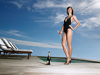 Woman in bathing suit holding champagne at poolside