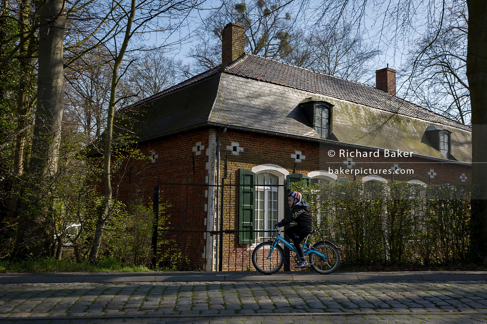 A young boy cycles past the gamekeeper's house at the entrance of the privately-owned de Merode Castle, on 25th March, in Everberg, Belgium. The gamekeeper's house lies alongside the cobbled Princes Lane (Prinsendreef) in Everberg and was built around 1770. The house was more familiar as the New Hostel (Nieuwe herbergh). This house was rented. Art historians described it as an 18th-century house in provincial regency style. In the end of the 19th century the house became the gamekeeper's house of de Merode Castle. The latter is the owner of the house as well. The gamekeeper's house is known in Everberg as the previous house of 'Jef van Vinus' or Jozef Meersman, who was the actual gamekeeper. <br /> <br /> <br /> <br /> on 25th March, in Everberg, Belgium.
