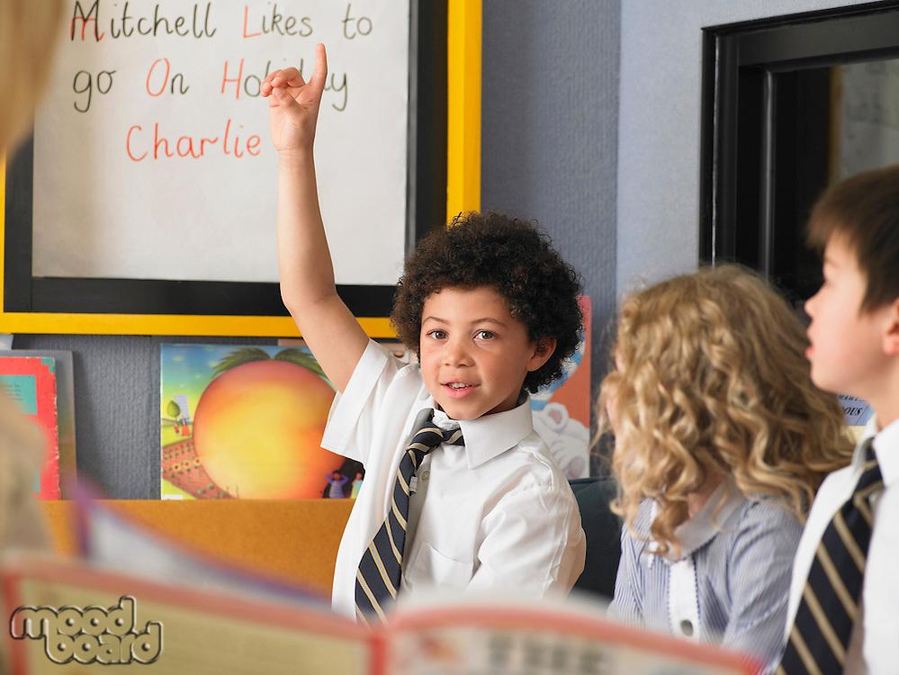 Elementary schoolboy raising hand in classroom