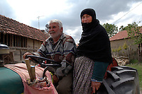 man and wife driving Tractor driving down main street of small rural village of Eymir in Anatolia Southern Turkey.