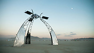 Huge, three legged solar powered future looking art instalation at dawn, Black Rock City, Burning Man Festival.