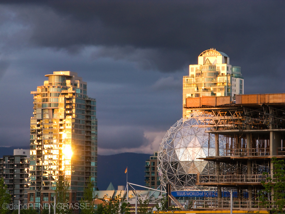 The setting sun is reflected in the windows of buildings on the east end of False Creek, Vancouver, in strong contrast to ominous clouds in the background. The construction of the athlete's village for the 2010 Olympic Games can be seen in the foreground.