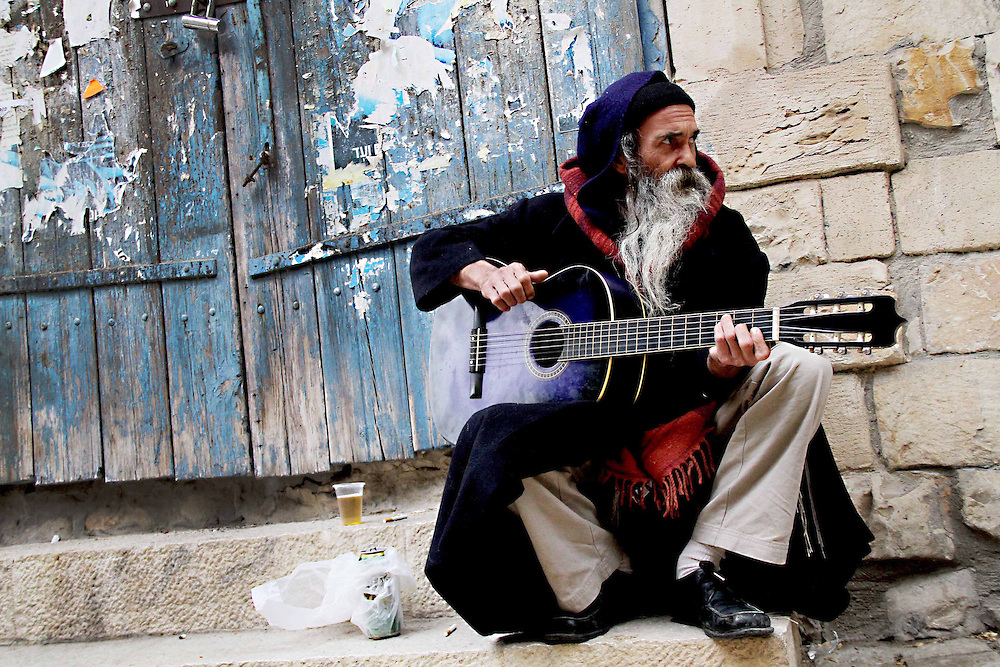 """A man plays his guitar in an alleyway in Tzfat, Israel Tuesday, January 4, 2011."""