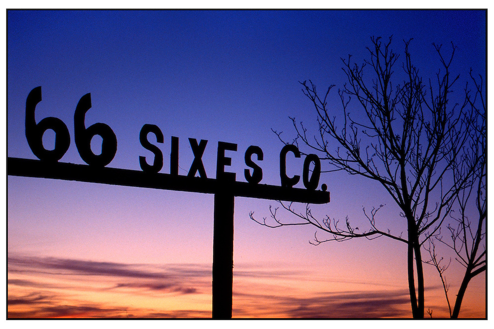 "A ""66 Sixes Co."" sign is seen against a sunset along a stretch of Route 66 near the city of Oro Grande, Calif.."