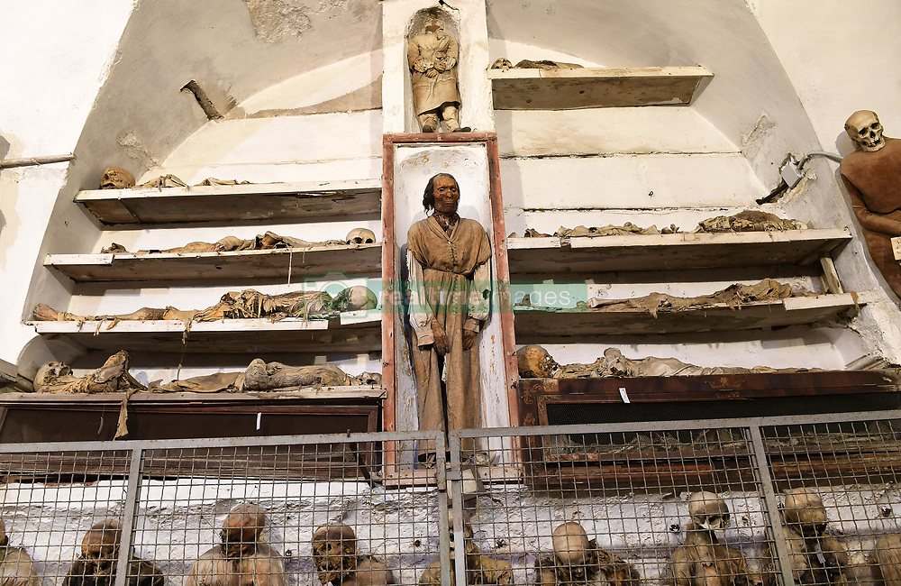 NO WEB FOR FRANCE - The Capuchin Catacombs of Palermo, Sicily, Italy on January 2019. In the center the mummified body of Antonio Prestigiacomo ( d.1844) one of the best preserved. The catacombs contain about 8000 corpses and 1252 mummies. Palermo's Capuchin monastery outgrew its original cemetery in the 16th century and monks began to excavate crypts below it. In 1599 they mummified one of their number, recently dead brother Silvestro of Gubbio, and placed him into the catacombs. The cemetery was first reserved for ecclesiastical workers, then accepted deceased from all walks of life, and experienced its greatest popularity during the 19th century. An inscription hanging from the neck or pinned to the chest, indicates the name, birth and death dates of the deceased.The cemetary was officially closed by civil order in 1880. But the last burials are from the 1920s. The cemetary has now become a kind of museum, filled with the forgotten dead, who are watched over by a group of Capuchin monks. Sicily will reveal over time a real research laboratory on mummification. It is spreading throughout the island and there is not an important village in sight that does not display the bodies of their priests, monks or citizens in the crypt of their church. Photo by Eric Vandeville/ABACAPRESS.COM