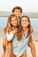 A teenage girl holds both her younger sister and little brother piggyback at the beach.