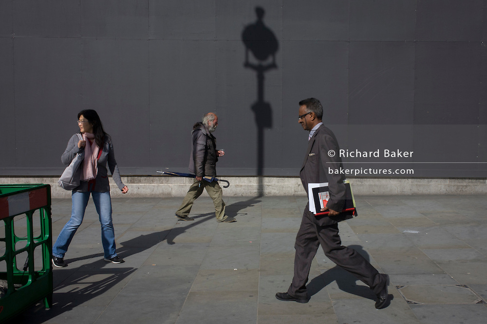 Man carries umbrella over the line of a lamp post shadow against a grey construction hoarding in central London's Trafalgar Square.