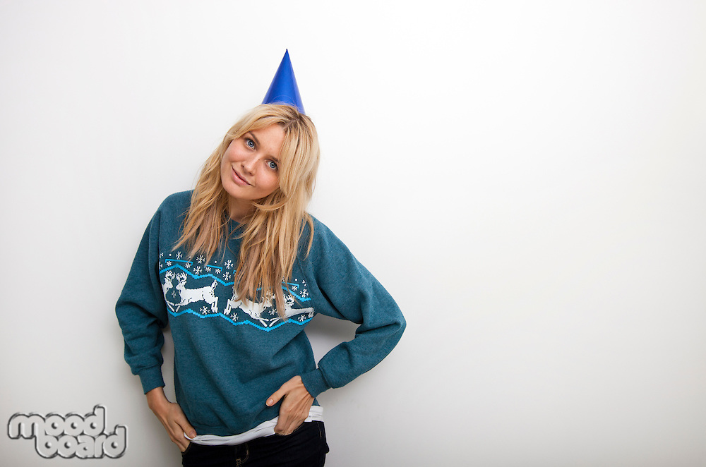 Portrait of woman in sweater wearing party hat against white background
