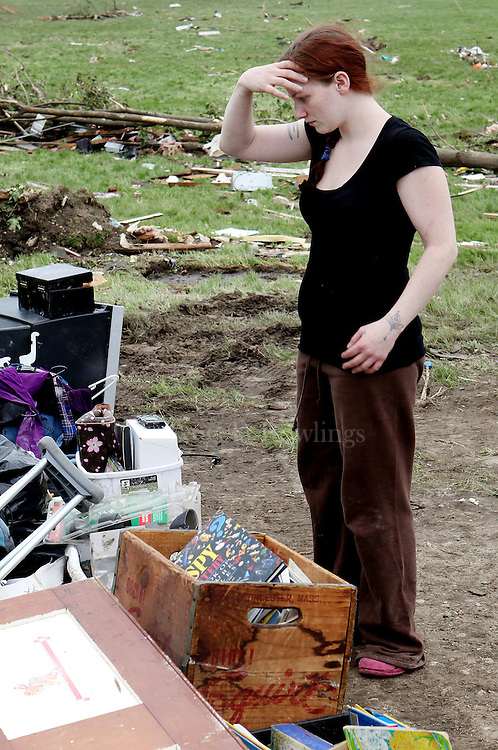 (060211  Monson, MA) Jessica Hansen, 25, looks over her belongings after her home was torn apart by a tornado, Thursday,  June 02, 2011.  Hansen and her family narrowly survived by crouching by the stairs when they had no time to escape to the basement.  Staff photo by Angela Rowlings.