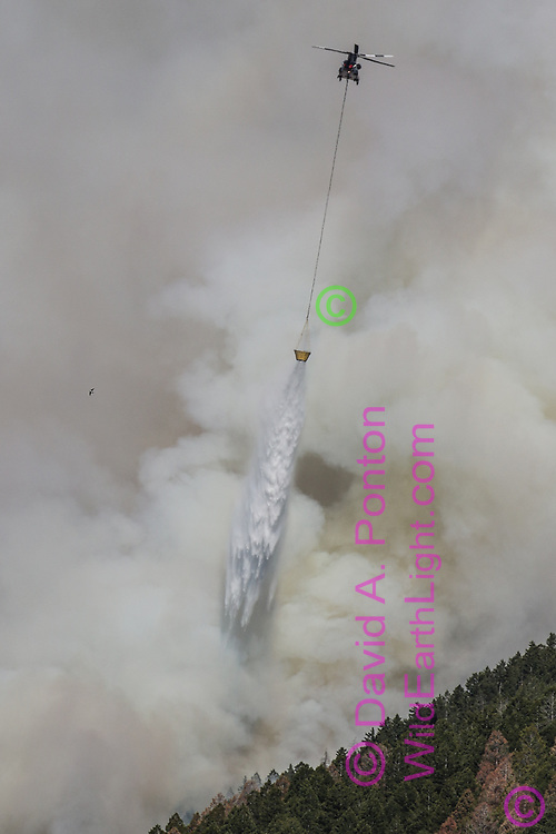 Helicopter drops water on the Cajete Fire burning mixed-conifer forest in the Jemez Montains, © 2017 David A. Ponton