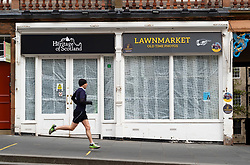 Edinburgh, Scotland, UK. 18 April 2020. Views of empty streets and members of the public outside on another Saturday during the coronavirus lockdown in Edinburgh. Man runs past closed tourist souvenir shop on the Royal Mile. Iain Masterton/Alamy Live News