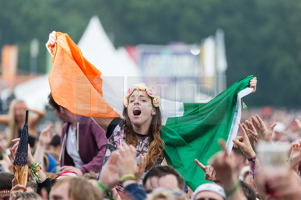 © Licensed to London News Pictures. 12/06/2015. Isle of Wight, UK.  A festival goer on their friends shoulders dances and listen to music waving an irish national flag in the pouring rain, as Irish band Kodaline perform on the main stage at Isle of Wight Festival 2015 on Friday Day 2.  Yesterday the weather was hot and Sunny.  This afternoon has seen torrential rain downpoors.  This years festival include headline artists the Prodigy, Blur and Fleetwood Mac.  Photo credit : Richard Isaac/LNP