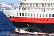 Hurtigruten cruise ship, Finnmarken, sails along snowy northern coast in early May near Havoysund, Norway.