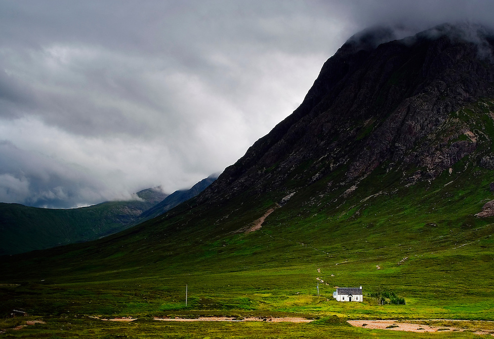 The modest white cottage shows the immense size and dominating landscape of the Glencoe area.