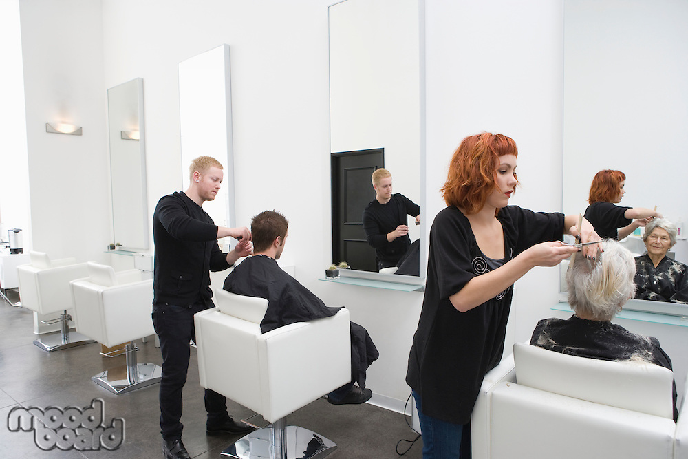 Stylists cut clients' hair in unisex salon