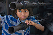 Kid on military gun<br /> Mabaruma<br /> GUYANA<br /> South America