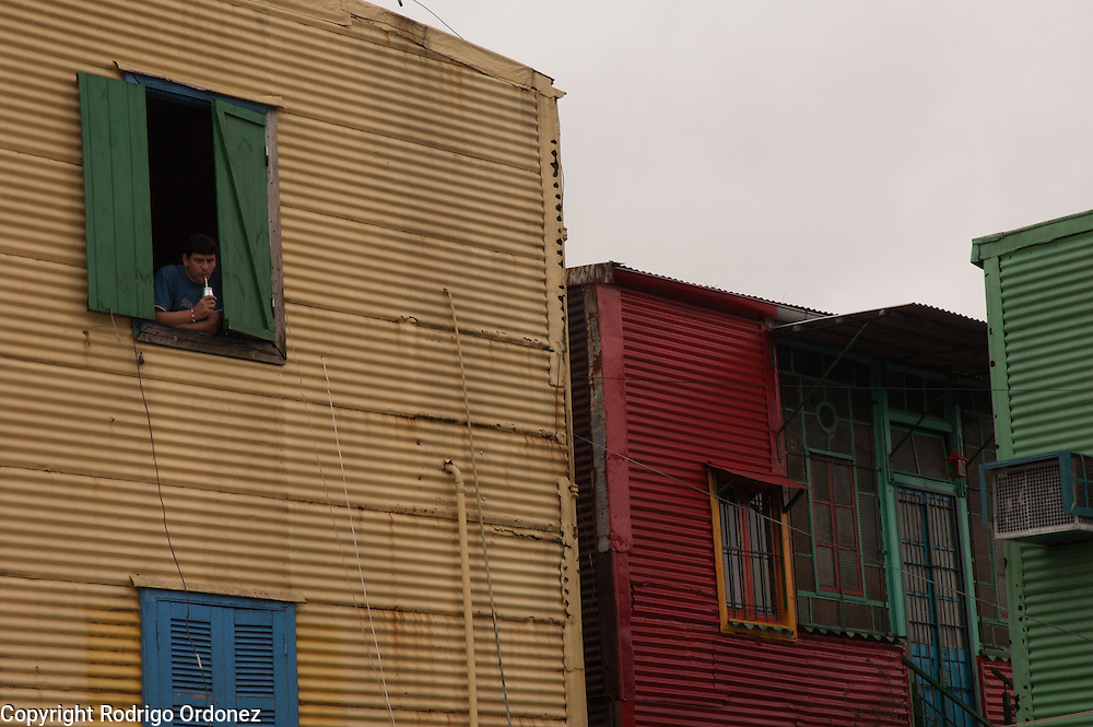 A man drinks mate while leaaning on a window at Caminito street, in La Boca neighborhood of Buenos Aires, Argentina.<br /> Caminito is a pedestrian street created in the late 1950s by local painter Benito Quinquela Mart&iacute;n and other artist friends to recreate a version of the old immigrant neighborhood of La Boca, using wood and corrugated zinc painted in bright colors. Today, Caminito and the surrounding areas feature cafes, souvenir shops, tango dancers and other street performances aimed to attract tourists.