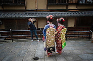 A Chinese-speaking tourist makes a snapshot for two Chinese-speaking women, with one of their smart phones.  There are many shops in the Kiyomizu district that will allow women to dress like a maiko, an apprentice geisha, for the fee.  Kyoto.  Japan.