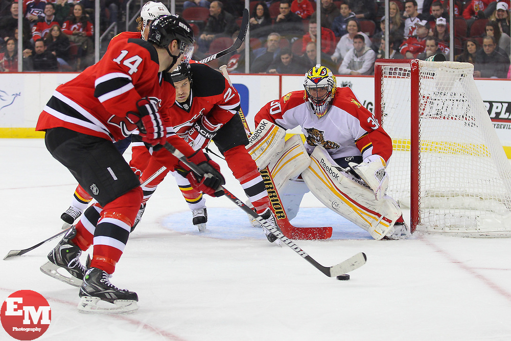 Mar 23, 2013; Newark, NJ, USA; New Jersey Devils center Adam Henrique (14) skates with the puck past the net of Florida Panthers goalie Scott Clemmensen (30) during the third period at the Prudential Center. The Devils defeated the Panthers 2-1.