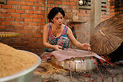A woman prepares rice paper in Cai Be, Vietnam.