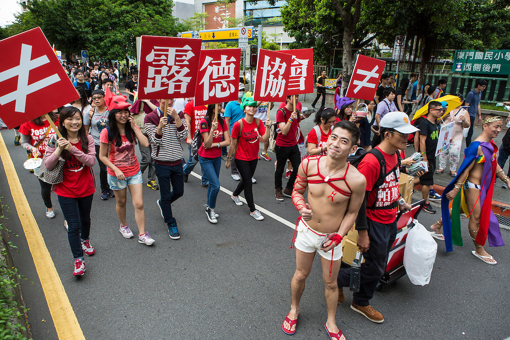 "A marcher from an HIV support group smiles as the pride parade moves through the city. The annual march through Taipei's city streets is the largest in Asia, with well over 50 000 people taking part. The 2014 event had the theme ""Walk in Queer's Shoes"", to encourage the wider community to lend their support for equal marriage rights."