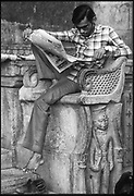 India. circa 1990.<br />Man on stone bench reading his daily newspaper. Jaisalmeer, Rajasthan.