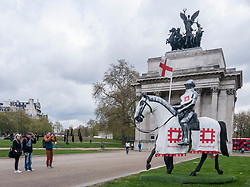 © Licensed to London News Pictures. 22/04/2015. Wellington Arch, London. Tourists take a photo as English Heritage unveil a 15ft St George at Wellington Arch in honour of the Patron Saint ahead of England's largest St George's Day celebration at Wrest Park as well as the launch of a nationwide tour which will see the knight open jousting tournaments at castles across England. Photo credit : Stephen Chung/LNP