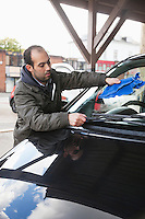 Employee wiping vehicle windscreen in car wash