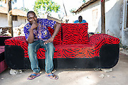 Hamidu Saidi sitting on a recently made sofa. One of the owners of Mnyangu Sofa Seat a local sofa making company, part of the VSO / ICS Elimu Fursa project (Opportunities in Education) Lindi, Lindi region. Tanzania.