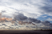 Big sky with clouds and smoke stacks from Athabasca Oil  Sands plant, Fort McMurray, Alberta, Canada