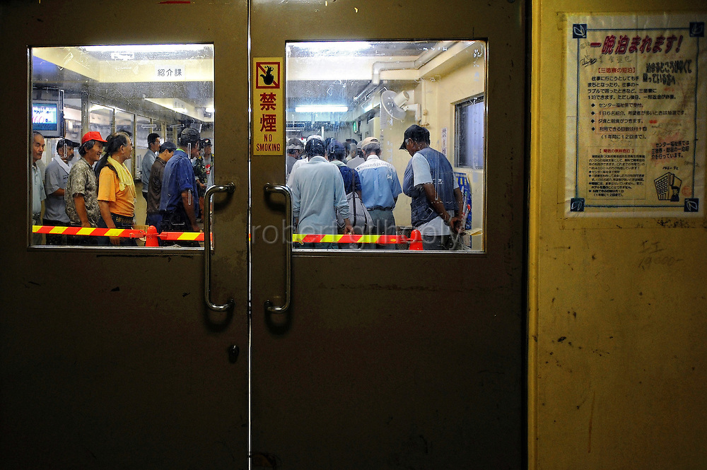 A notice by the door informs of free accommodation for homeless people needing a bed for the night as around 30 homeless men line up to enquire about possible work placements at the Nishinari Labor Welfare Center in the Kamagasaki district of Osaka, Japan. Thousands of homeless people flock to the center daily in hope of securing day labor work, such as hands on building sites - jobs that pay around 50 pounds per day..