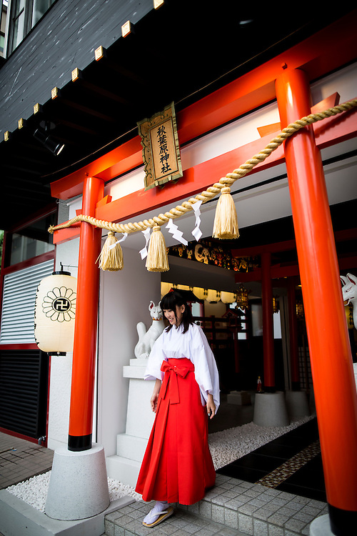 "TOKYO, JAPAN - JUNE 27 : A shrine maiden walks out of the shrine entrance of Akihabara shrine in Akihabara, Tokyo, Japan. June 27, 2016.  A newly opened Akihabara Shrine offers a memorial services for ""deceased"" anime figures. Photo by Richard Atrero de Guzman"