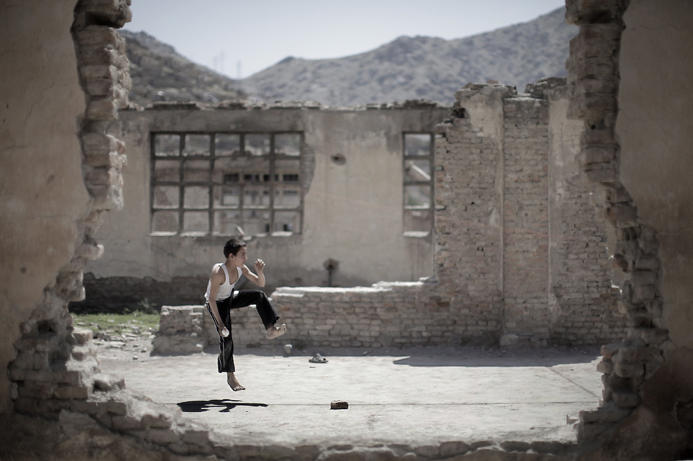 "An Afghan boy prepares to bowl a ball while playing cricket inside the ruins of a compound, which use to be home to a timber manufacturing factory in the late 80's, on the western outskirts of Kabul on May 14, 2010. Two NATO soldiers fighting in Afghanistan to quell a Taliban-led insurgency were killed in attacks, the military said. One was killed in an ""insurgent attack"" in the east of the country and the other died after a crude Taliban-style bomb exploded in the south on May 13, NATO's International Security Assistance Force said. AFP PHOTO/Mauricio LIMA"