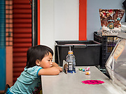 03 AUGUST 2019 - ST. PAUL, MINNESOTA: The child of a shopkeeper watches a video on his smart phone at the Hmongtown Marketplace. Thousands of Hmong people, originally from the mountains of central Laos, settled in the Twin Cities in the late 1970s and early 1980s. Most were refugees displaced by the American war in Southeast Asia. According to the 2010 U.S. Census, there are now 66,000 ethnic Hmong in the Minneapolis-St. Paul area, making it the largest urban Hmong population in the world. There are two large Hmong markers in St. Paul. The Hmongtown Marketplace has are more than 125 shops, 11 restaurants, and a farmers' market in the summer. Hmong Village is newer and has more than 250 shops and 17 restaurants.    PHOTO BY JACK KURTZ