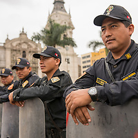 National police officers stand guard in the Plaza Mayor, or main square, of Lima, Peru.