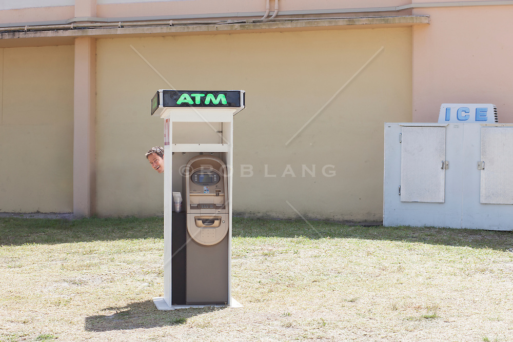 man peaking his head out from behind a rural ATM machine