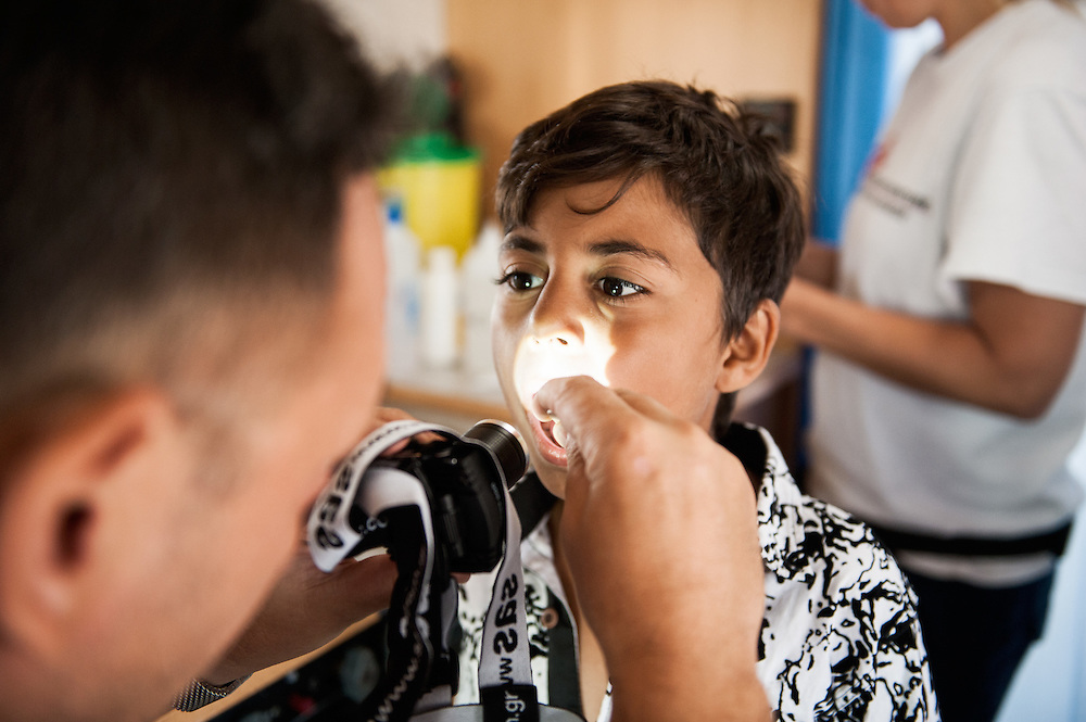 Six year old Mohammed from Iraq is checked by MSF doctor Dimitris Giannousis at the mobile camper van of MSF at Mytiline port, Lesvos, Greece.