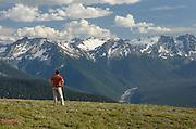 Hiker contemplating the peaks of the Upper Suiattle River, Glacier Peak Wilderness North Cascades Washington
