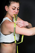Young Woman measures the circumference of her arm. She may be keeping track of weight loss during a diet but compulsive body analysis may be a symptom of a body image disorder such as anorexia nervosa. Model Released