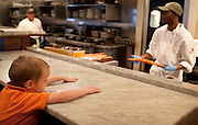 Hagen Dickinson, left, looks on as his pizza is made during lunch at BRIO Tuscan Grill in Murray, Friday, Nov. 9, 2012.