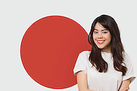 Portrait of smiling mixed race young woman against Japanese flag