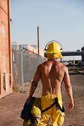 back of a shirtless muscular fireman outdoors