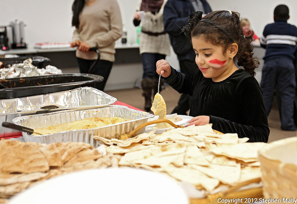 Zaynab Tafish, 6, of Waterloo, works her way down the food line at the celebration of the first anniversary of the Egyptian revolution for democracy at the Muslim American Society, 2121 North Towne Lane NE in Cedar Rapids on Wednesday evening, January 25, 2012. The evening's activities included various speakers, a video documentary about the revolution, and a meal. (Stephen Mally/Freelance)