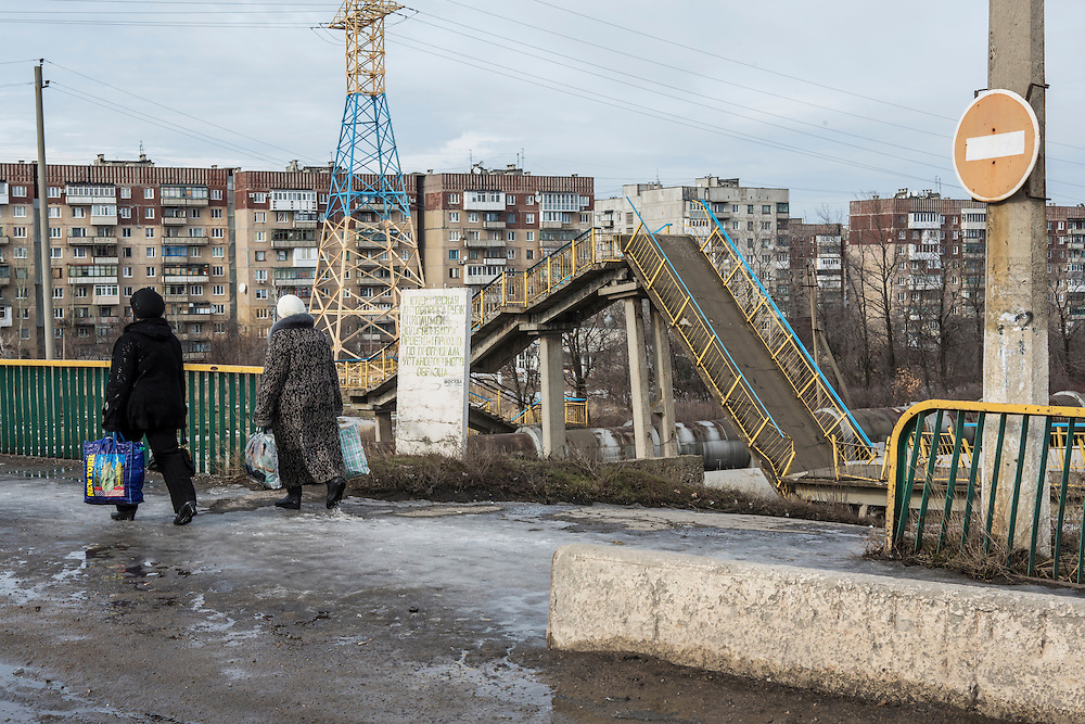 GORLOVKA, UKRAINE - JANUARY 31, 2015: Women walk past a foot bridge that was destroyed by shelling in Gorlovka, Ukraine. Fighting in Ukraine has intensified over the last week, with rebels declaring the end of a September ceasefire. CREDIT: Brendan Hoffman for The New York Times