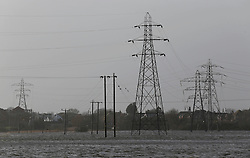 © Licensed to London News Pictures. 06/01/2014, Christchurch, UK. Electricity power line towers stand in a flooded field at Christchurch, England , Monday, Jan. 6, 2014. Part of UK continue to be affected by floods and strong wind. Photo credit : Sang Tan/LNP