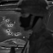 A Mexican soldier stands guard by a bullet riddled vehicle in which two men were executed by drug cartel assassins in Culiacan, Sinaloa, Mexico..(Credit Image: © Louie Palu/ZUMA Press)