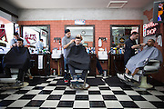 From left to right, owner Alex Franco, Fabi Gomez, and Garrison Finks, trim customers' hair at Alex's Classic Barber Shop & Shaves in Fremont, California, on April 9, 2014. (Stan Olszewski/SOSKIphoto)