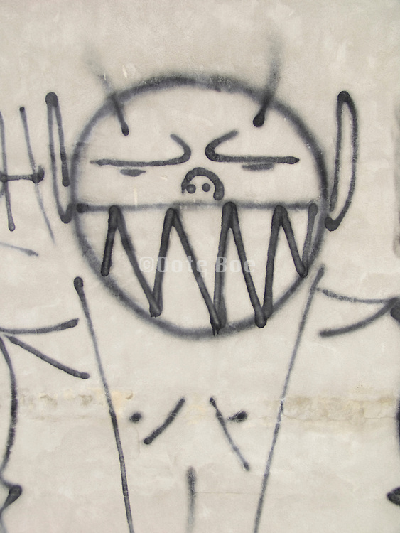 a big smiling graffiti portrait on a gray wall
